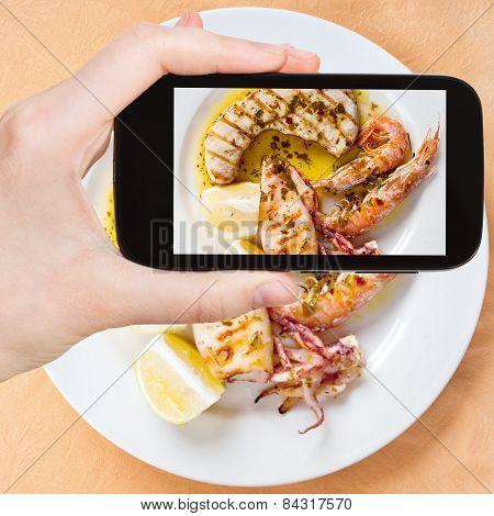 Tourist Taking Photo Of Sicilian Grilled Fish Mix