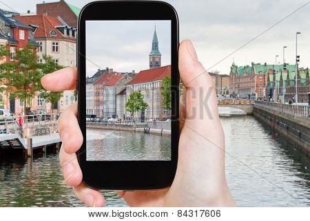 travel concept - tourist taking photo of Copenhagen cityscape on mobile gadget Denmark poster