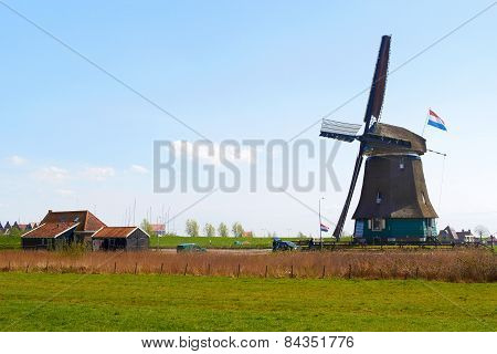 Sunny Dutch landscape in springtime with green grass and an historic mill.