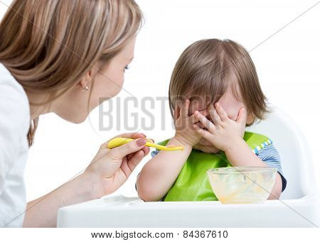 Little boy refuses to eat closing face by hands