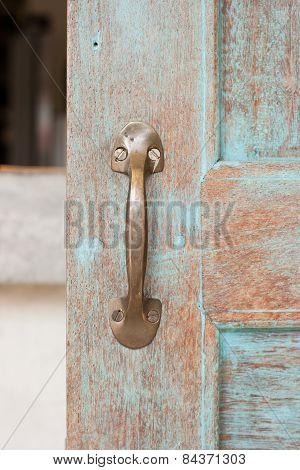 The old retro brass doorhandle on the old wooden door. poster