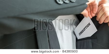 Businessman removing or placing a white card with word Corruption in the inner pocket of his suit jacket close up view of the card. poster