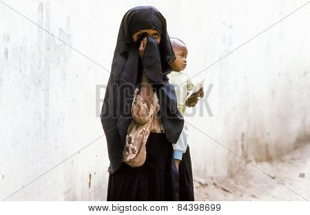 Arabic Unknown Mother Carries Her Baby In A  Wraparound Garment