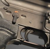 Close up of a gun trigger, square shot with a shallow depth of field poster