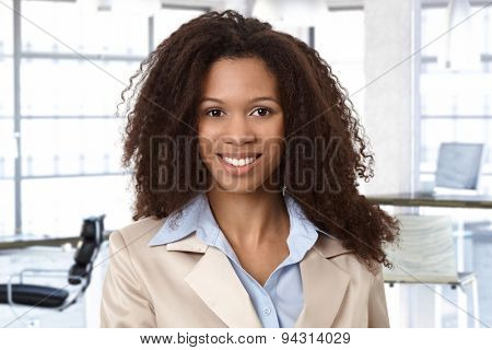 Portrait of attractive african woman at office, looking at camera, smiling.