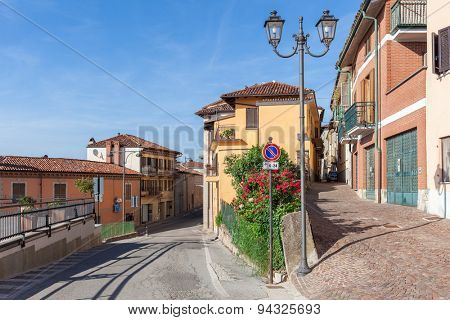 Narrow streets and lamppost among colorful houses in town of La Morra in Piedmont, Northern Italy.