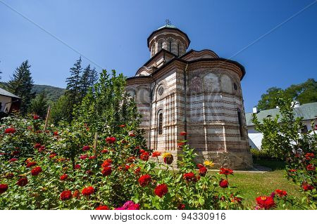 Cozia Monastery Church With Red Flowers On A Sunny Summer Day