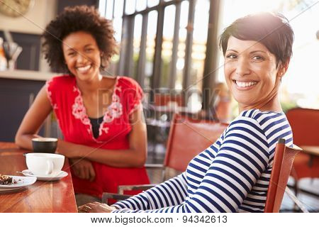 Two female friends meeting at a coffee shop
