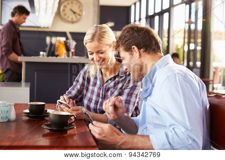 Man and woman using smart phones at coffee shop