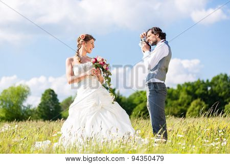 Wedding groom photographing bride with camera outside on field or meadow