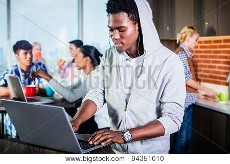 Black programmer in lounge of IT start-up coding software on his laptop, colleagues in the background