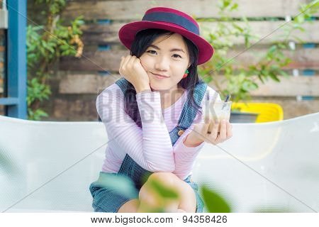 Portrait Of Happy Woman With Mug In Hands Sitting On Bench