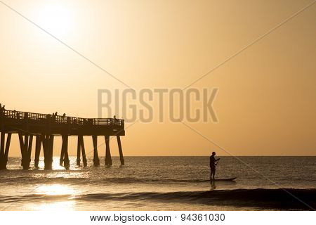 Silhouette of a man paddle boarding in the ocean.