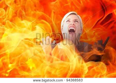 Upset woman screaming with hands up against fire