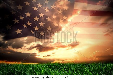 United states of america flag against green grass under blue and orange sky