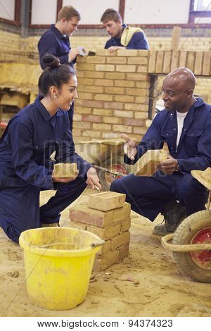 Teacher Helping Students Training To Be Builders
