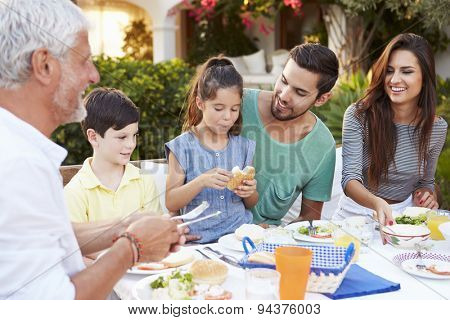 Multi Generation Family Eating Meal At Outdoors Together