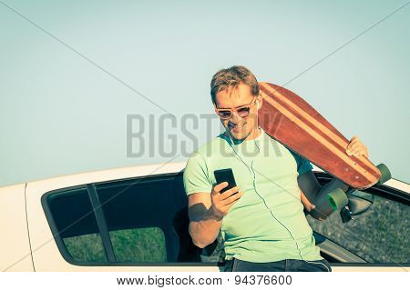Young Male Hipster Man Model With Smartphone Listening Music During Trip Break Next His Car