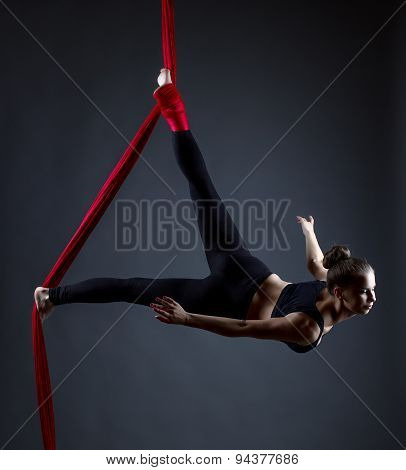 Studio shot of graceful female acrobat posing at camera poster