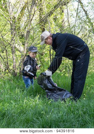 Zugres, Ukraine - April 26, 2014: Father And Son Clean Debris From The City Park