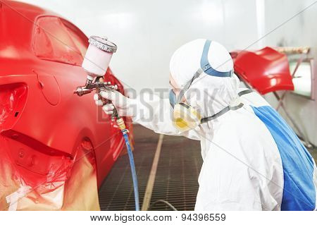 auto painting worker. red car in a paint chamber during repair work