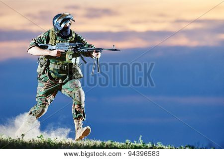 military. soldier in uniform running with machine gun weapon on sunset during attack outdoors. Authentic shooting in challenging conditions. Maybe little blurred.