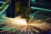 metal working. Laser cutting technology of flat sheet metal steel material processing with sparks. Authentic shooting in challenging conditions. Maybe little blurred. poster
