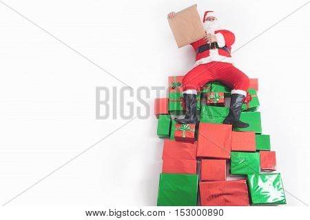 Santa sitting at the top of many big gift boxes and reading wish list. Black Friday 2016 at United States. Wishes. Copy space at white background. Cristmas shopping. Xmas, New Year Merry Christmas