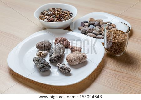 Plates full of stonesgravel and sand on a table
