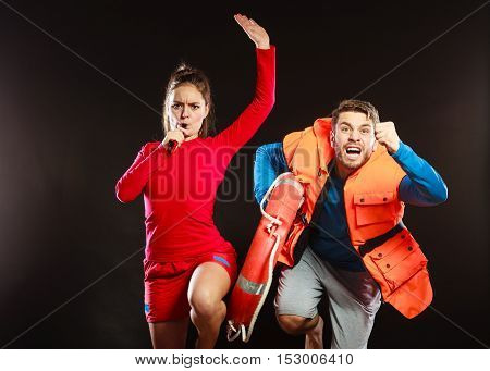 Lifeguards with rescue ring buoy lifebuoy and life vest jacket running to accident. Man and woman supervising swimming pool whistling on black.
