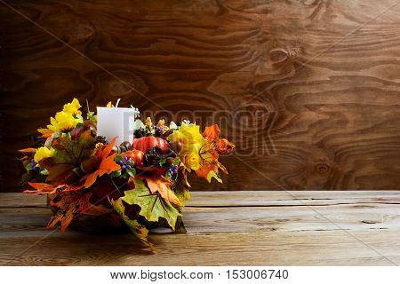 Thanksgiving decoration with silk leaves on rustic background. Thanksgiving greeting with fall decor. Fall centerpiece. Thanksgiving background. Copy space.