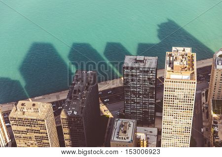 Aerial view of skyscrapers and their shadow on the water of a lake. Vintage colour filter applied. Photo from helicopter in Chicago.