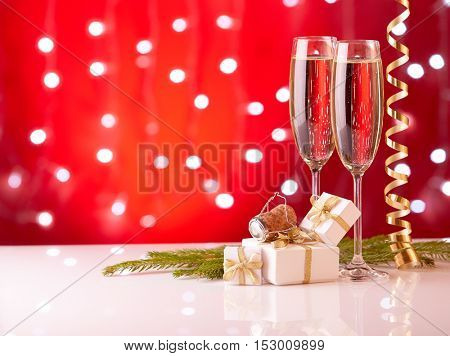 Two glasses with champange, fir tree branch, gift boxes and christmas decorations on a red background with lights of garland.  New year and Christmas.