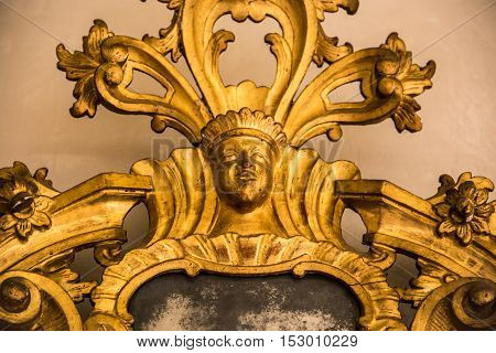 Detail of a carved gilded frame of an antique mirror.