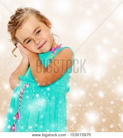 Caucasian little tanned girl in a smart blue dress. The girl put her hands to the ear.Brown festive, Christmas background with white snowflakes, circles.