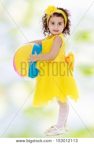 Pretty dark-haired little girl in a bright yellow dress and a bow on my head with a striped ball. Girl posing sideways to the camera in full growth.white-green blurred abstract background