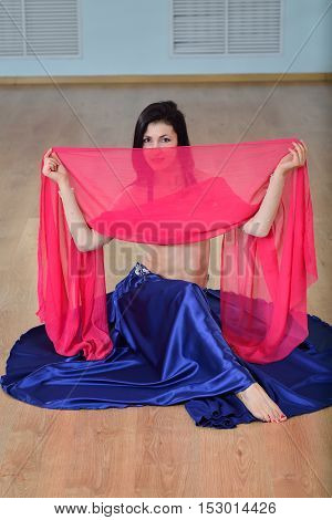 Beautifull caucasian woman in costume for belly-dance is dancing indoors at fitness class covered in silk veil.