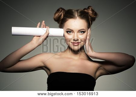 Beautiful girl listens in the paper roll. Woman couting news and gossip.