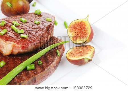 main entree : roasted beef lamb steak served with hot cayenne peppers green chives and sweet figs on plate isolated over white background
