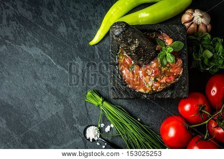 Traditional Latin American mexican Tomato sauce salsa, chilean chancho en piedra in stone mortar and ingredients tomatoes, chile, garlic, onion, dark slate stone background. Top view. Copy space