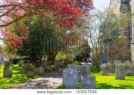 RYE, UK - 1 MAY, 2016: St. Mary church yard with ancient grave stone and spring's blossom trees