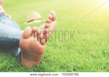 Feet of asian woman relaxing on grass field with flowers background. Relaxing concept.