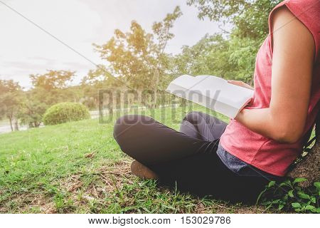 Woman relaxing outdoors looking happy and reading a book. Morning with a book. Relaxing concept. Retro filter effect soft focus selective focus.