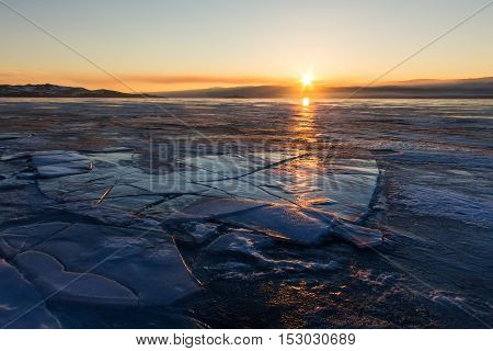 Cracks In The Blue Ice Of Lake Baikal At Sunset. Olkhon Island