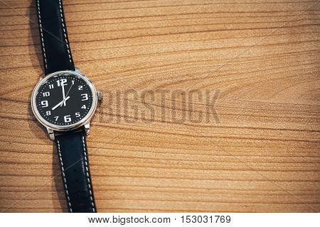 wristwatch on wooden table with blank space for text on the right side - clock face show the time on 8 o'clock morning