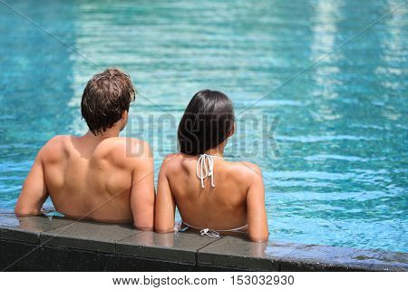 Honeymoon couple relaxing on the edge of an infinity swimming pool in luxury resort spa retreat. Hotel travel vacation. Relaxation concept. Unrecognizable people from behind enjoying summer holidays.
