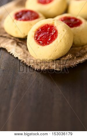 Thumbprint Christmas cookies filled with strawberry jam photographed with natural light (Selective Focus Focus on the lower edge of the jelly filling on the first cookie)