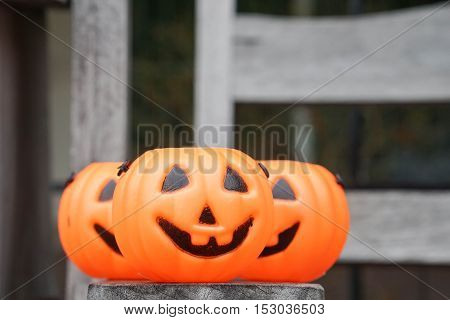 close up three orange Jack-O-Lantern on wooden bench