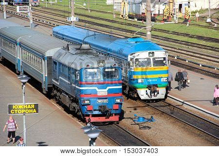 Orsha, Belorussia - Aug 18, 2016: Diesel and electric suburban trains standing on the tracks of the railway station waiting for passengers. Summer evening.