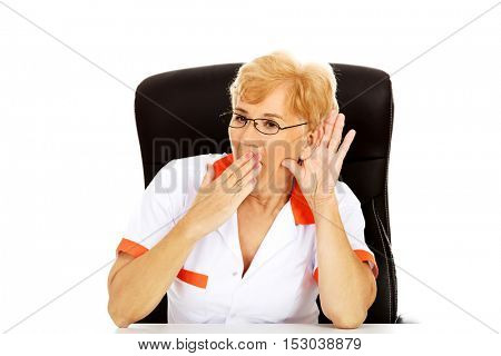 Shocked elderly female doctor or nurse sitting behind the desk and overhears a conversation